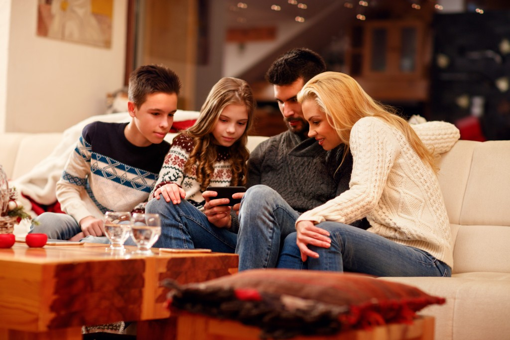 smiling family playing game on mobile phone on Christmas holidays